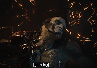 """Darkseid lying in his ship, wounded and unconscious. The closed caption says """"grunting."""""""