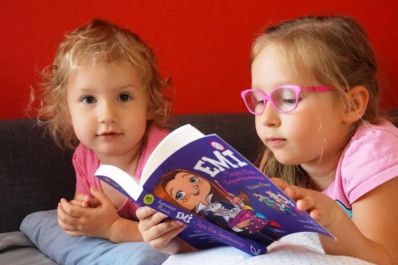 sześciolatka czyta książkę Emi i tajny klub superdziewczyn