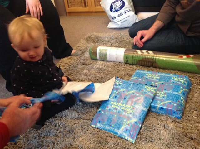 baby sat on floor with presents