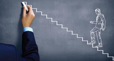 A imagem mostra uma pessoa desenhando com um giz em quadro negro a ilustração de um homem subindo escadas até o topo