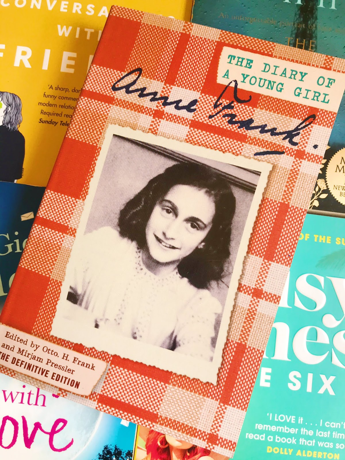 The Diary of a Young Girl by Anne Frank laid on top of 4 other books