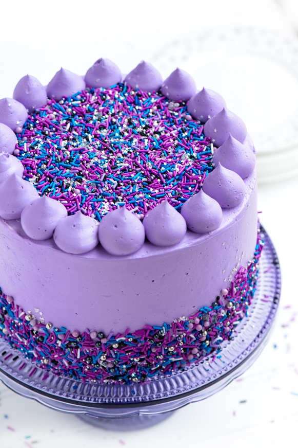 Galaxy Layer Cake - Moist layers of flavourful black velvet cake filled with fluffy cream cheese filling and fresh blackberries, frosted in gloriously purple vanilla bean frosting and finished with Sweetapolita Galaxy Twinkle Sprinkle Medley and buttercream poofs.