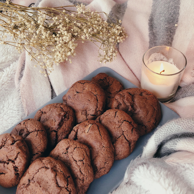 A plate of chocolate cookies next to a candle