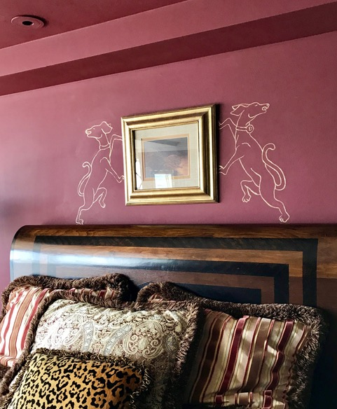 Dogs painted on wall above bed