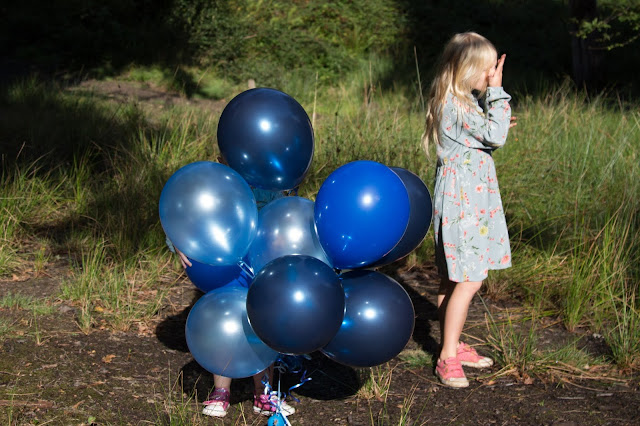 A small pair of feet poking out from a bunch of balloons next to a girl looking sideways and wiping her nose