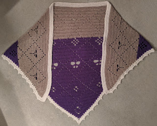 A finished crochet shawl in purple and beige with a cream border. The shawl has a pattern of a grid with butterfly, flowers and dragonfly motifs in the grid.