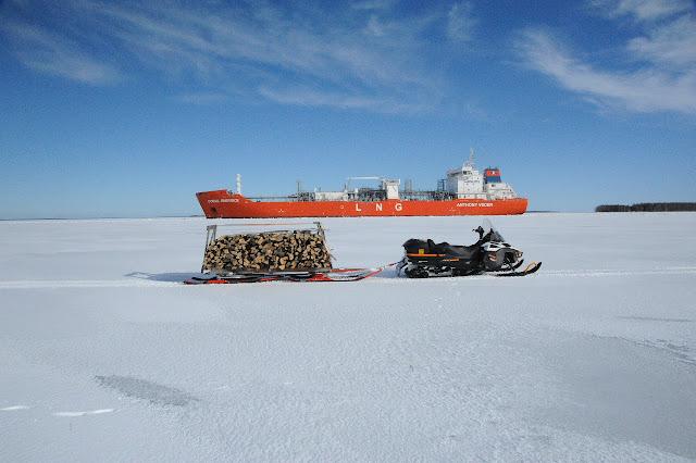 Tankkeri kulkee jäissä ja etualalla halkokuormassa oleva moottorikelkka