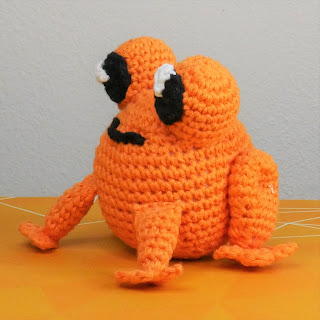 A orange crochet frog made with cotton yarn, slightly angled away from the camera.
