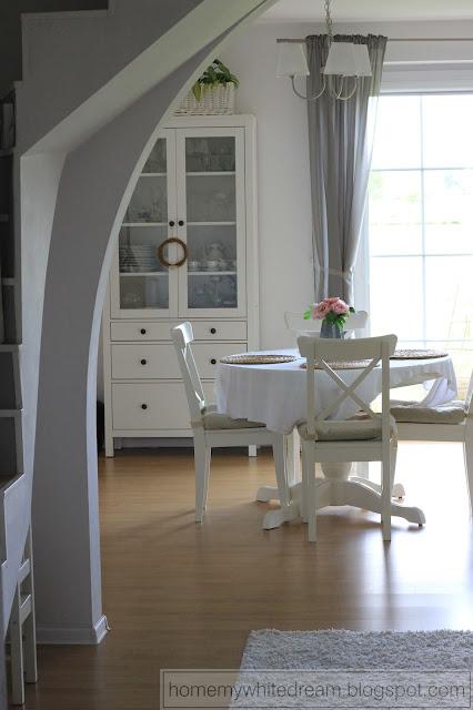biały salon, drewno w salonie, drewniana ściana w salonie, biała witryna Hemnes, biały stół i krzesła, Atrapa kominka DIY, biało czarne poduszki, wiklinowy fotel