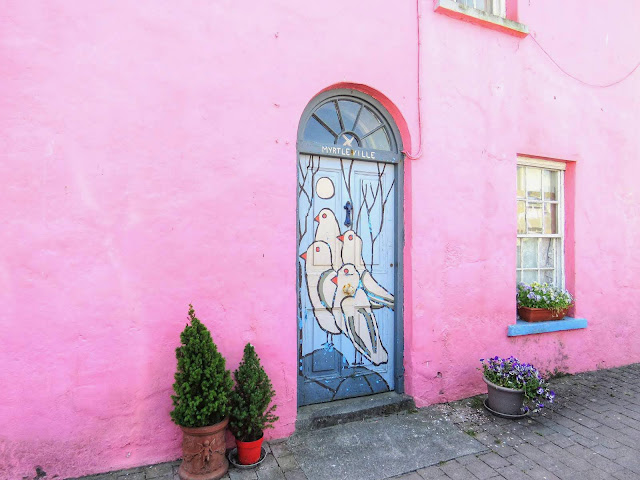 Pink house with a door decorated by painted birds in Ardmore Ireland