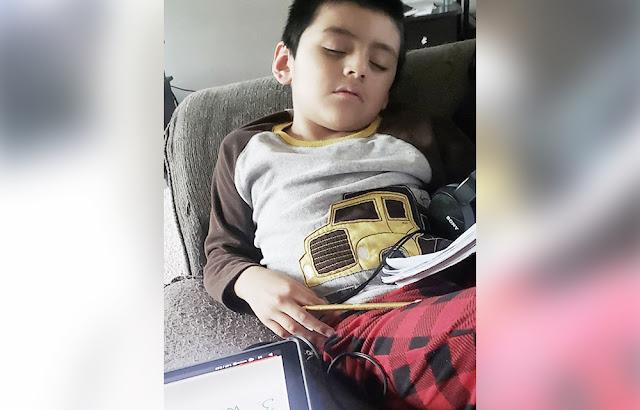 Filho criança cansada com tarefas da escola cochilando