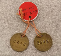 two round brass disks, about 3/4 inch in diameter, both have the number 3942 stamped in them as identification for the miner