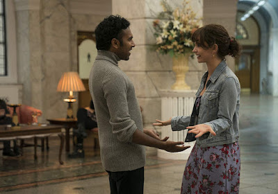 Jack Malik (Himesh Patel) and Ellie (Lily James) are reunited in a hotel lobby in a movie still for the film Yesterday