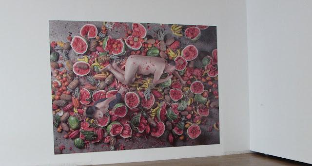 Foto em grande formato de frutas e homem e criança no meio delas
