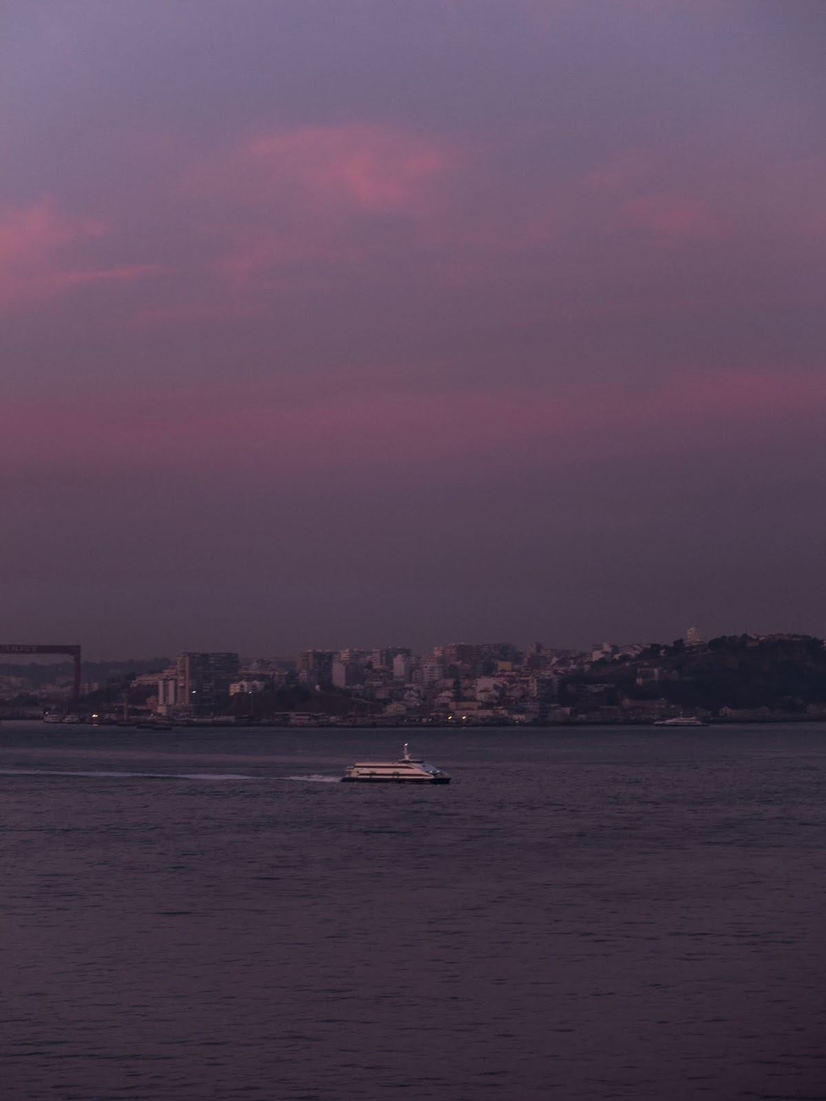 Purple sunrise over the water in Lisbon, Portugal.