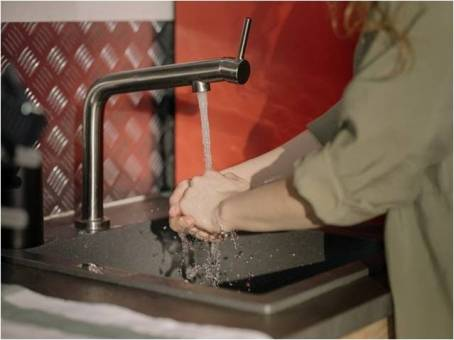 a woman washing her hands under a steady stream of water