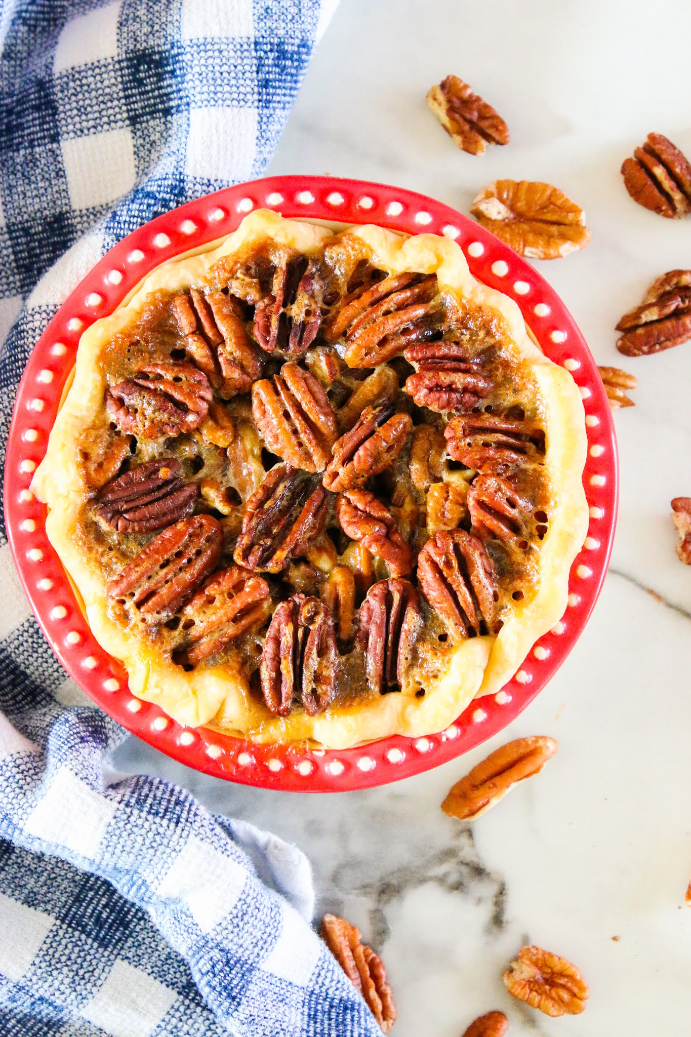 Pecan pie in a red pie dish with a blue dish towel in the background.