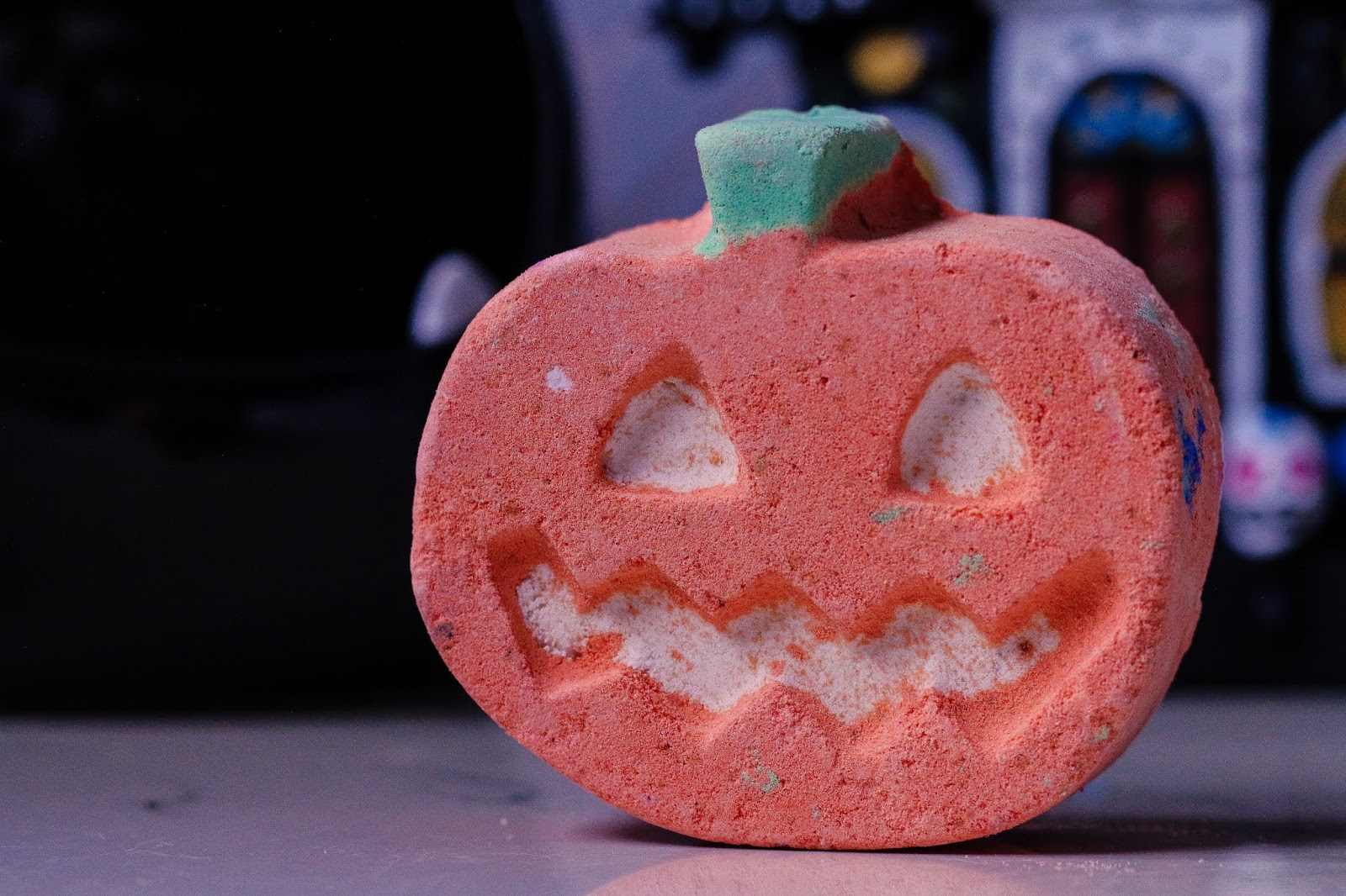 extreme close up photo of the Pumpkin Pumpkin Bath bomb from lush. An orange bath bomb that is shaped like a pumpkin with glow in the dark eyes, a green stem at the top and a white pumpkin mouth. Bath bomb sitting on white marble bed side table with a Haunted house Halloween decoration in the background.