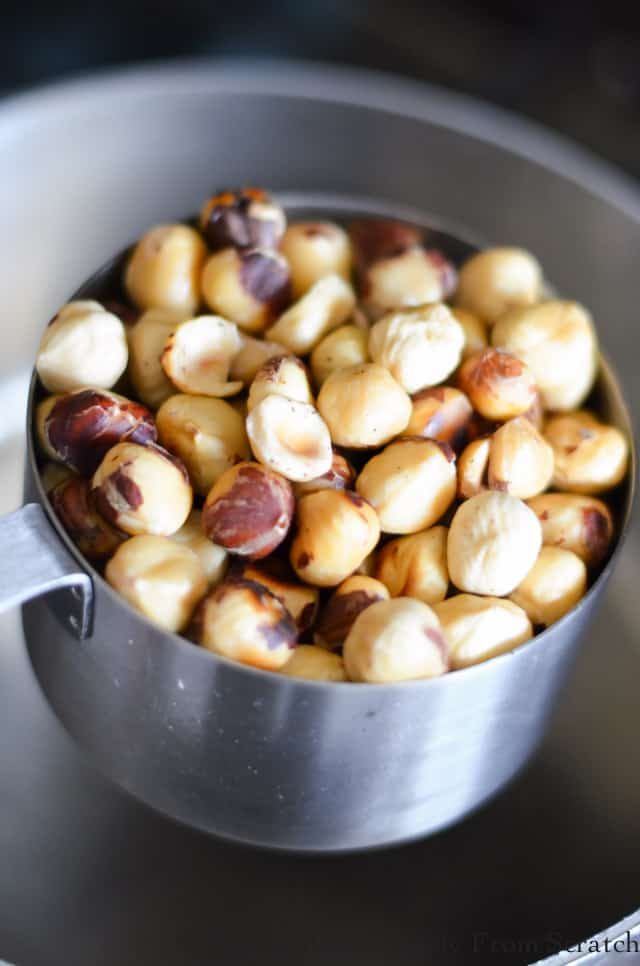 Peeled Hazelnuts in a measuring cup to make Candied Hazelnuts.