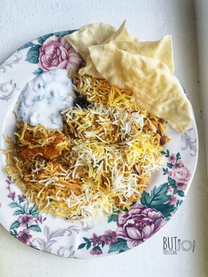 A plate of Kacchi Mutton Biryani with raita and pappad