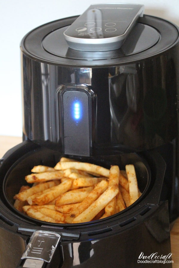 Placing seasoned fries into the air fryer basket to cook