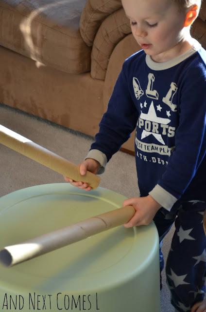 Preschooler drumming with cardboard tubes on a large bucket