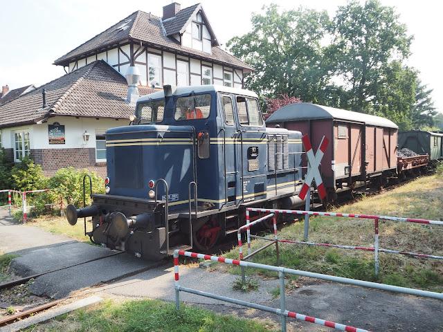 Vor einem alten Bahnhofsgebäude von Börnsen steht der Zug