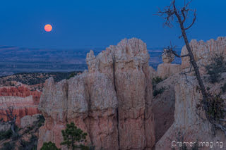 Cramer Imaging's fine art landscape photograph of a red moon rising over rock formations of Bryce Canyon National Park Utah