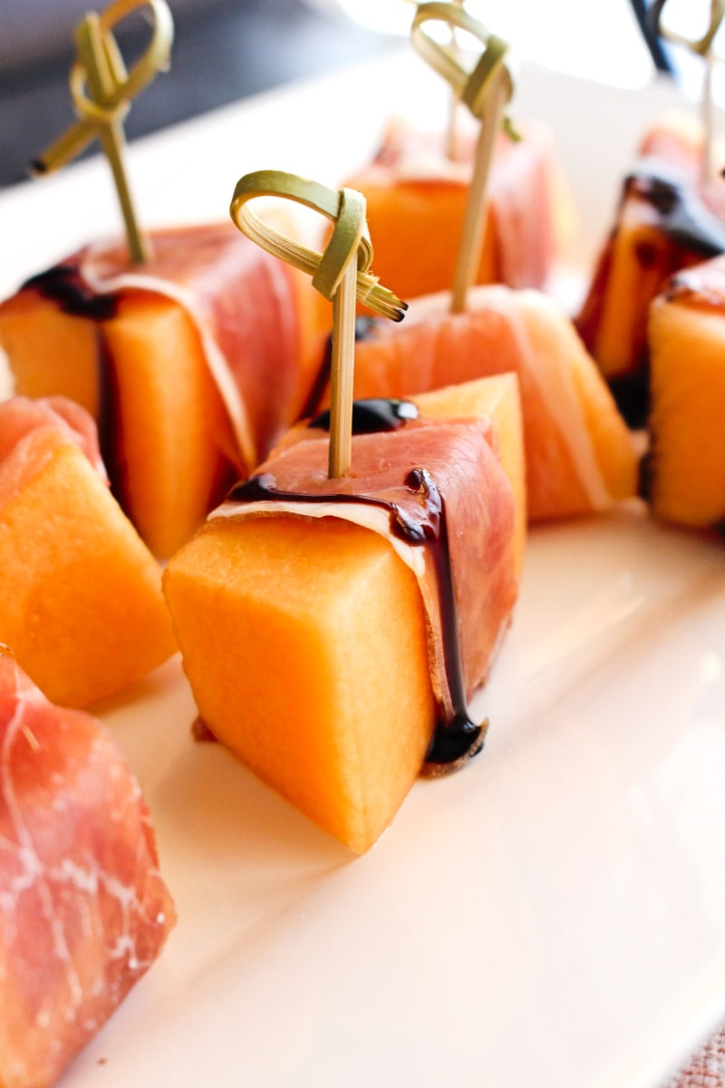 Side view of proscuitto wrapped cantaloupe on a white plate with a pink background
