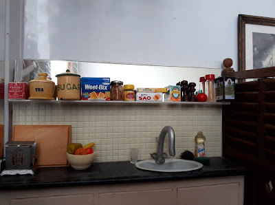 1/12 scale modern miniature scene of a kitchen bench with a fold-down toaster, chopping board and bowl of fruit on it. Next to the sink is a glass, a scourer, a sponge and a bottle of washing-up liquid. On the shelf above are two containers of tea, a cannister of sugar, a packet of Weet-Bix, a half-used jar of jam, a jar of vegenite, a packet of Sao crackers and a packet of Lemon crisp biscuits, a box of barley sugars, a salt and pepper grinder, a tomato-shaped tomato sauce bottle, a jar of spaghetti and a cask of red wine.