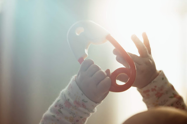 image shows newborn hands holding a large toy nappy pin