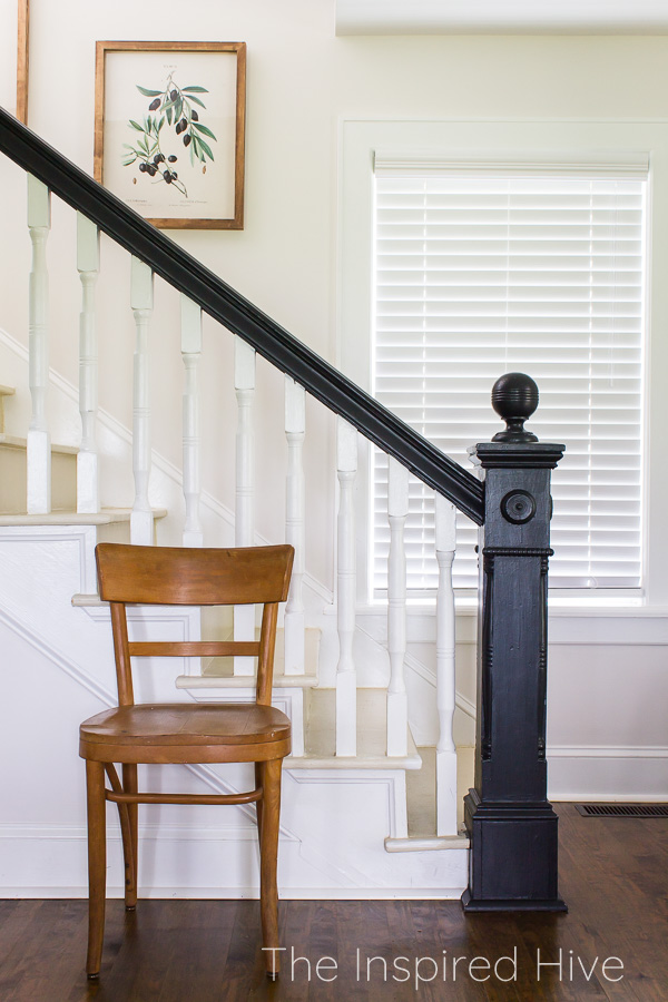 100 year old staircase with black newel post and banister and white balusters. Antique chair.