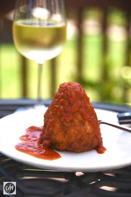 Homemade Sicilian arancino with gravy (tomato sauce)