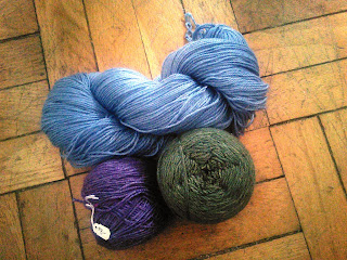 a twisted skein of sky blue yarn, a yarn cake of purple yarn, and a yarn cake of dark green yarn