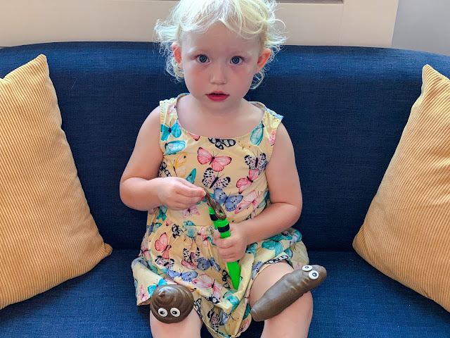 a 3 year old holding a slingshot poop with poop on each knee