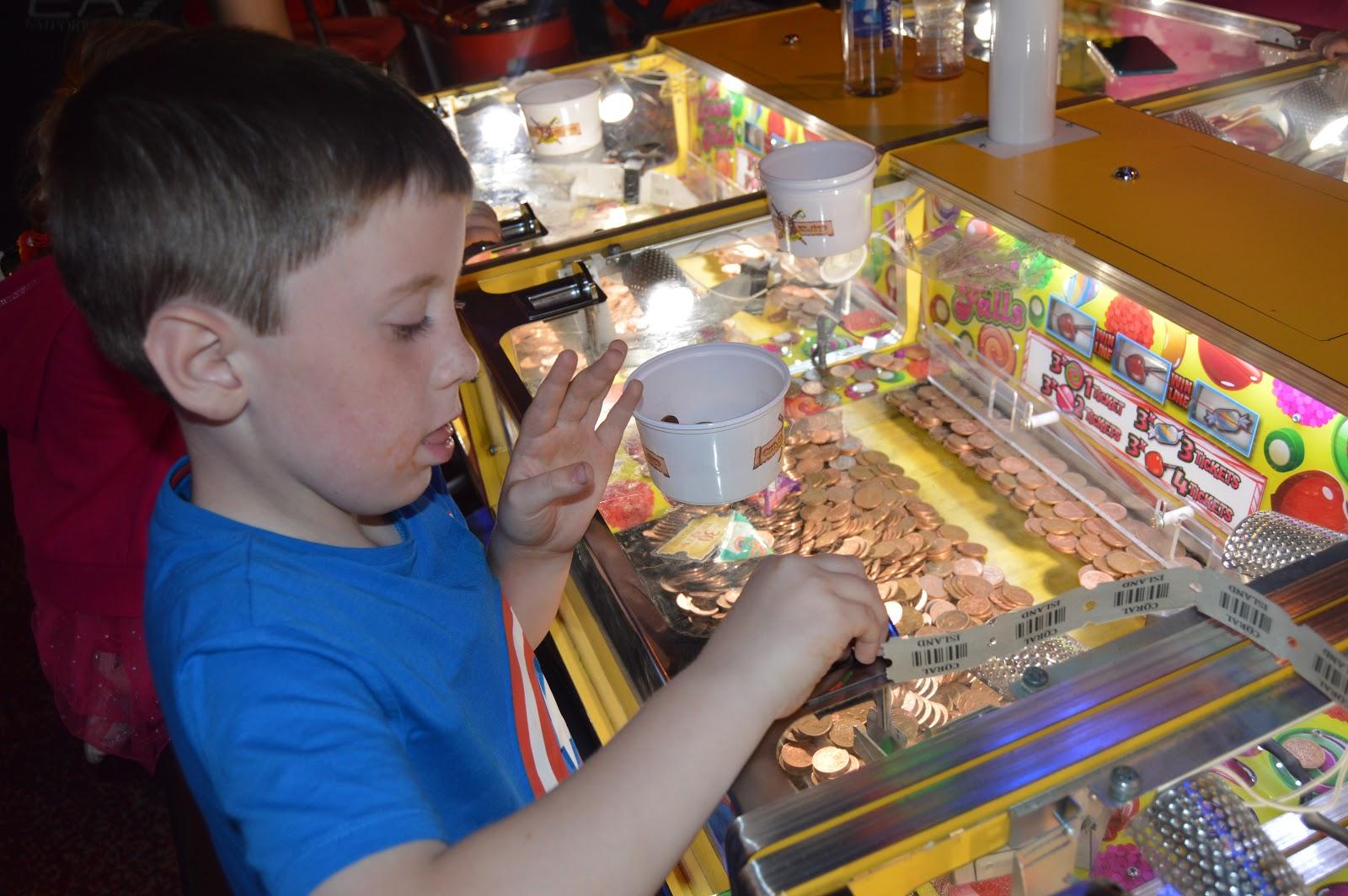 boy playing on penny aracde