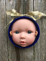 An ornament with a gold bow hanging on a grey wall. It is a baby doll face with two tiny reaching around by the ears.