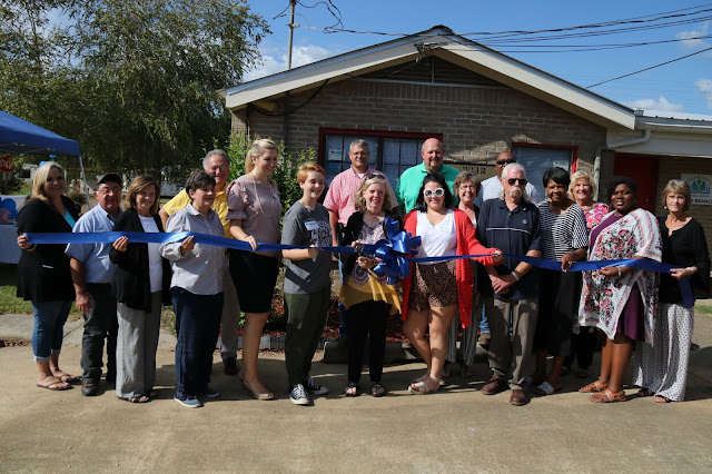 A large group of people hold up a blue ribbon and stretch it out in front of them. A woman in the middle holds a pair of scissors, ready to cut the ribbon..