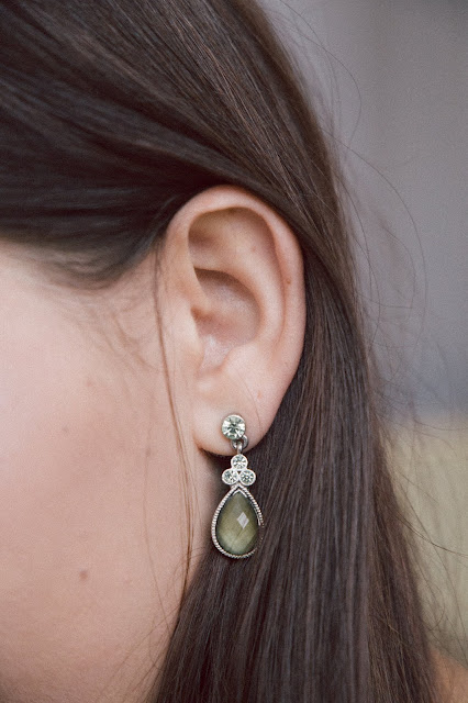 Close up of a green teardrop earring on an ear.