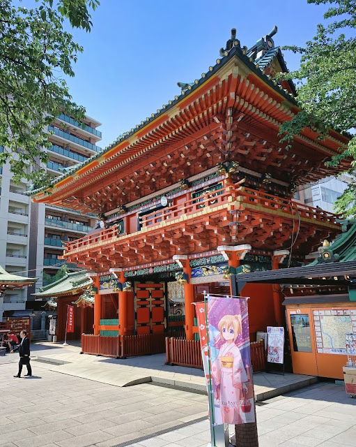 Facade of the Kanda Myojin Shrine with Japanese locals and tourists walking around and a still image banner of an anime girl wearing pink traditional summer kimono