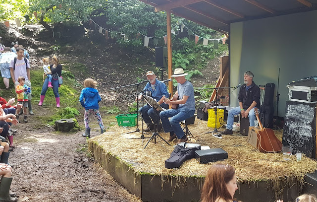 The Workshy Fops band performing 3 musicians singing playing cajon and 2 guitars woodland stage Just So Festival 2019