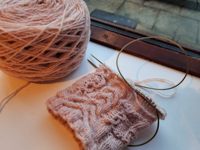 A cake of pink yarn and some test knitting are sitting on a white windowsill.  You can see paving flags through the window