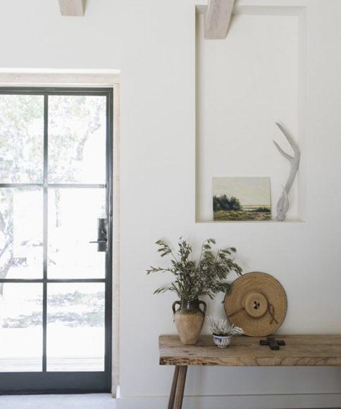 Grandes ventanas para que entre mucha luz, paredes blancas y muebles de madera