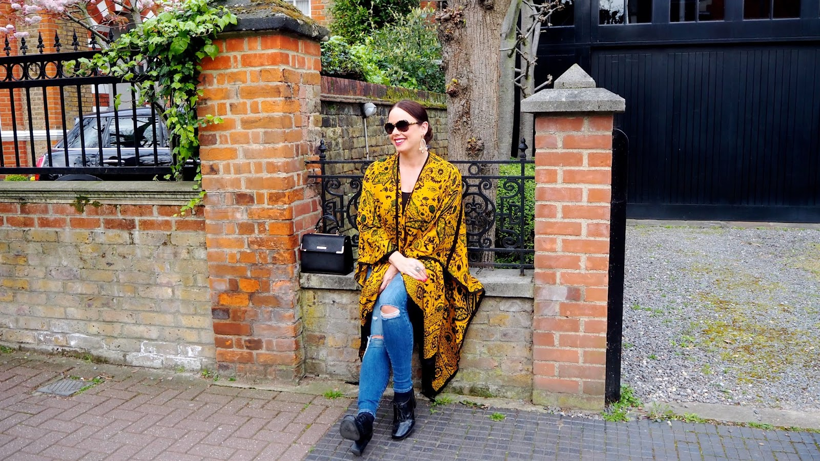 Mustard paisley kimono cape with black fringe trim with ripped jeans