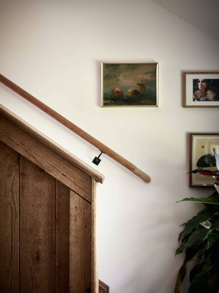 Un ático con una reforma de cocina low cost: escalera con arrimadero de madera y barandilla de hierro.