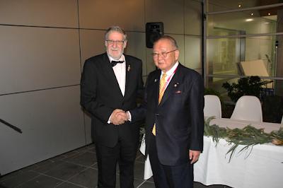 ディビッド・シモンズ会長と握手をする吉田会長