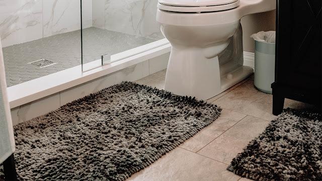 Bathroom floor with gray, fuzzy bath mats.