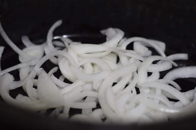 Sliced onion in the bottom of the crockpot.