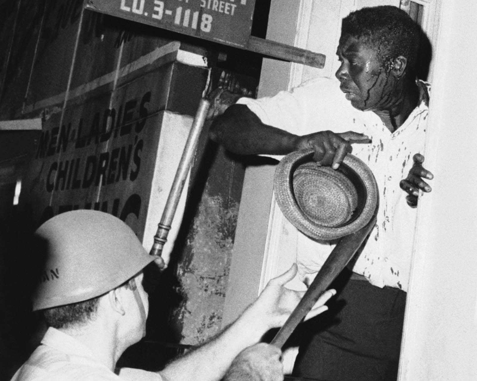 A man, his shirt stained by blood running down his face, is cornered in a doorway by club-wielding police early August 30, 1964 in North Philadelphia, Pennsylvania. The man had been clubbed for refusing to move along.