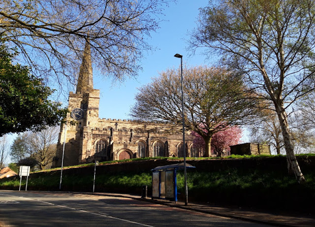 Image shows St Oswald's Church, Winwick, in the sunshine with blossom trees in the churchyard